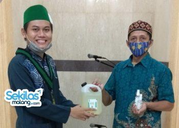 Foto: Penyerahan hand sanitizer oleh Kader HMI Komisariat Teknik UM pada salah satu warga
